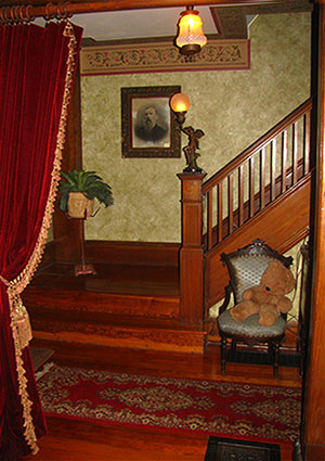 Entrance hall after refinishing staircase, with stenciled walls and velvet portiers