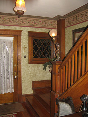 Entrance hall after refinishing staircase, with stencilled walls