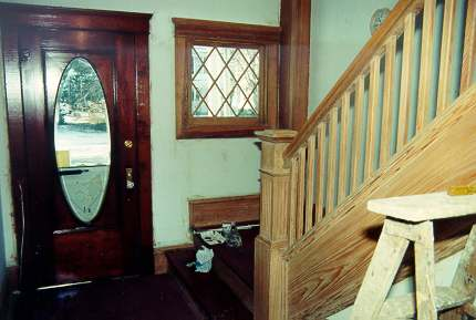 Entrance hall showing stripped, unfinished staircase