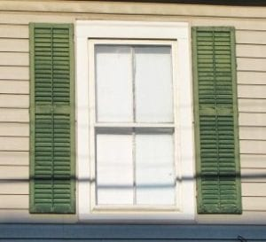 real wood shutters mounted next to window casing