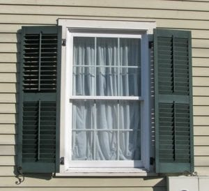 green wood louvered window shutters